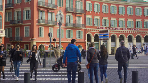People crossing street near red building of Caisse D'epargne Cote D'azur Live Action