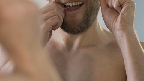 Man with beard flossing his teeth properly, mouth health care, closeup video Footage