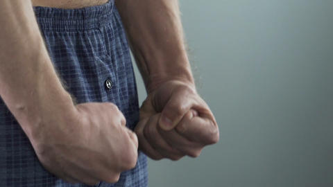 View on male clenching his fists, man's strength and health, potency. Close-up Live Action