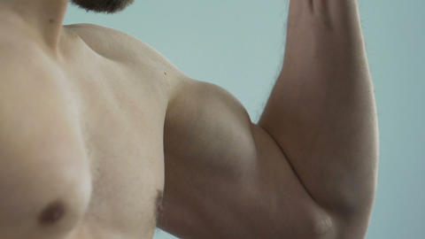 Strong person clenching fist and showing biceps into camera, masculinity Footage