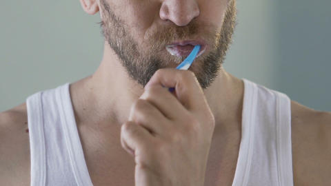 Bearded male brushing teeth, everyday morning ritual, hygiene and health Live Action