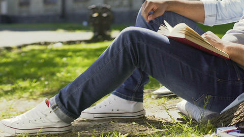 Teenager enthusiastically reading book sitting outdoors and breathing fresh air Footage