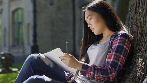 Inspired young asian female artist drawing outdoors, student enjoying hobby Footage