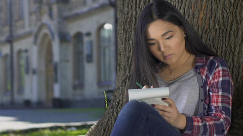 Concentrated girl writing love letter to her boyfriend dreaming about meeting Footage