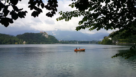 Romantic couple floating in rowboat on lake Bled Live Action