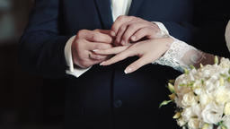 Hands of bride and groom exchanging wedding rings GIF