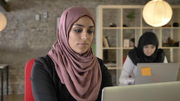 Portrait of young muslim women working, serious, two womens in hijab sitting and Footage