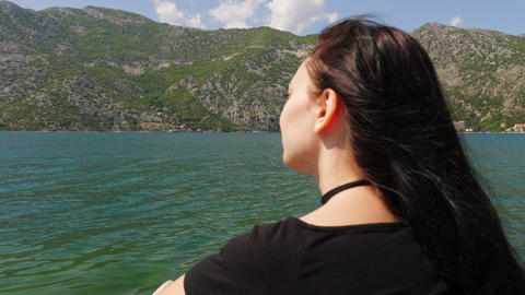A young woman looks at the water and mountains GIF