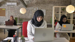 Three young muslim womens in hijab working in modern office, beautiful female Footage