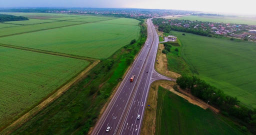 Highway between green fields. Beautiful road. Cars go on the highway. Bird's-eye Footage