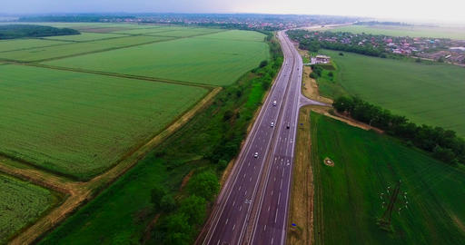 Highway between green fields. Beautiful road. Cars go on the highway. Bird's-eye Live Action