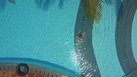 woman goes out pool under tropical tree ビデオ