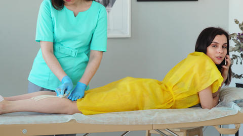 The girl talks on the phone and smiles during hair removal on her legs Live Action