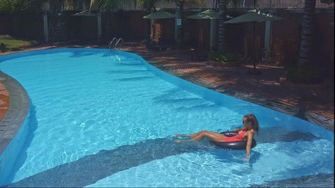 blond girl swims on inflatable ring in pool Footage