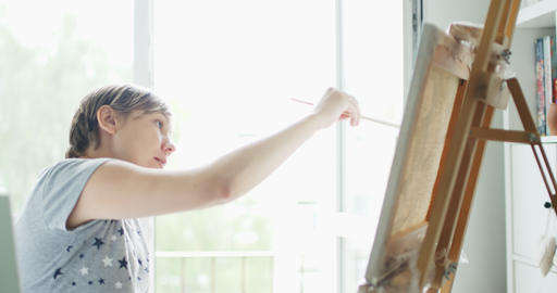 Woman artist draws picture on canvas in home studio Footage