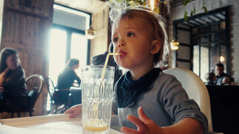 Baby boy drinks orange juice glass sitting at table in cafe Footage