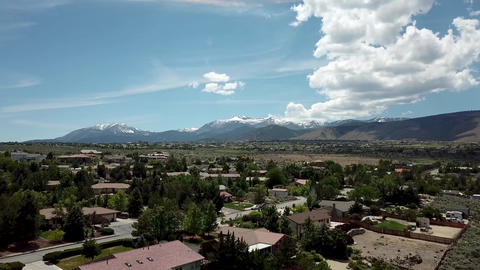 aerial, white clouds over American town on the background of the mountains Archivo