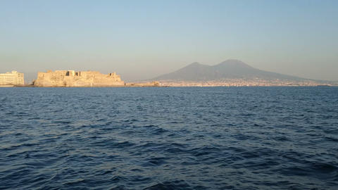 View from the sea of Castel dell'Ovo and Mount Vesuvius in Naples, Italy Footage