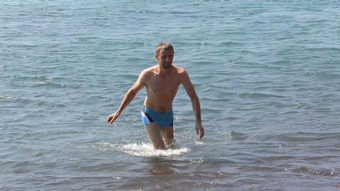 Happy man refreshing in cool sea water, walking towards shore, active rest Live Action