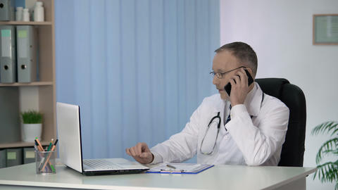 General practitioner giving online and phone consultations, servicing patients Footage