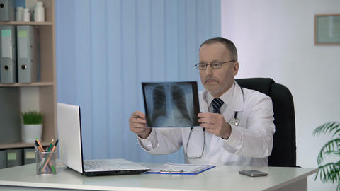 Experienced radiologist carefully examining and describing X-ray image of lungs Footage
