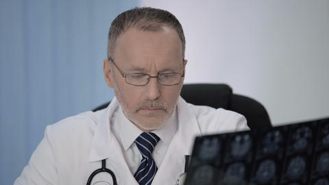 Neurosurgeon writing data from MRI after surgery for comparison with previous Footage