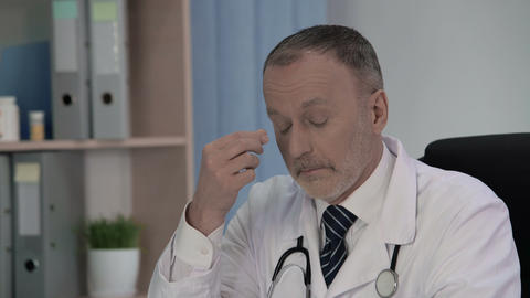 Weary male doctor thinking about medical cases that occurred in his practice Footage