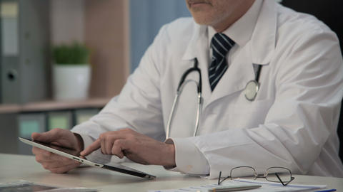 Doctor scrolling medical app on tablet to learn about medication novelties Live Action