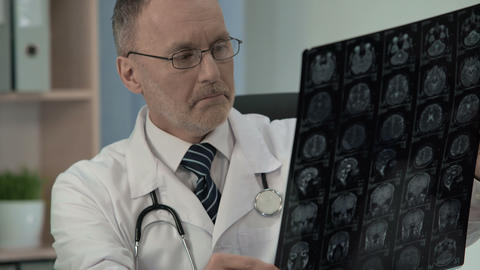 Medic studying MRI and making sure of serious disease writing mail to colleagues Footage