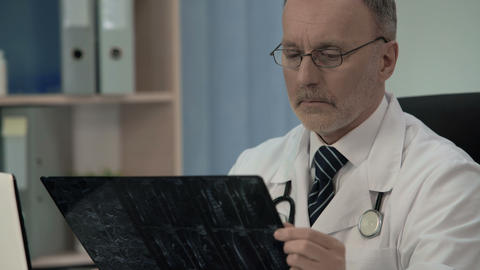 Traumatologist looking at x-ray, diagnosing vertebra weakness in patient's neck Live Action