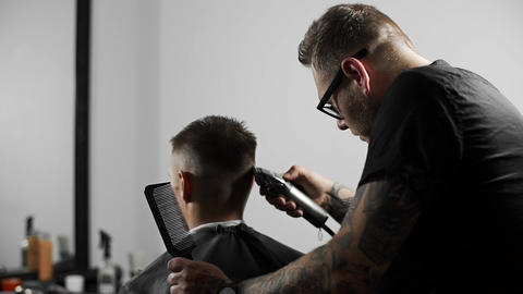 Tattoed barber makes haircut for customer at the barber shop by using Footage