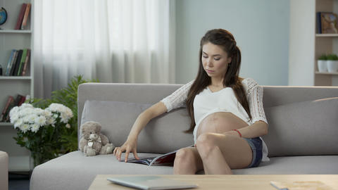 Young pregnant female sitting on sofa, reading magazine, relaxing leisure time Footage