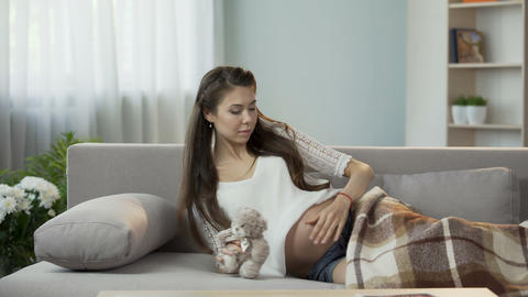 Young pregnant lady putting herself down to rest, holding teddy bear, future kid Footage