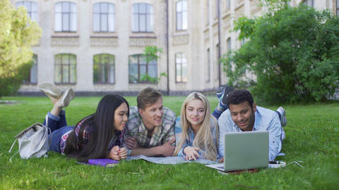 Multi-ethnic students lying on grass and watching funny video on laptop, friends Footage