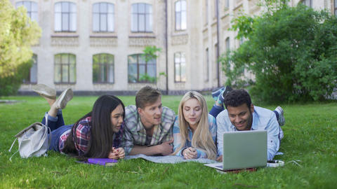 Group of multi-ethnic students relaxing on grass and watching video on laptop Footage