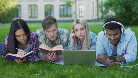 Mixed-race students lying on grass and preparing for exams, university education Footage