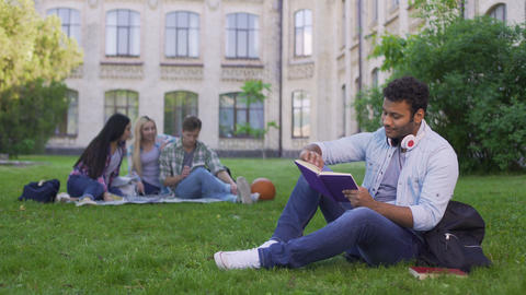 Happy biracial male student sitting on grass and reading interesting book Live Action