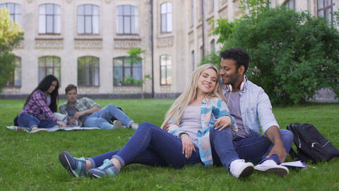 Multiracial couple relaxing on grass, talking and smiling, first love, students Live Action