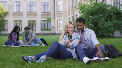 Loving couple of students sitting on lawn and watching video on smartphone Footage