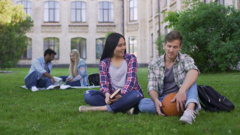 Students sitting on lawn on campus and flirting, male trying to impress girl Footage