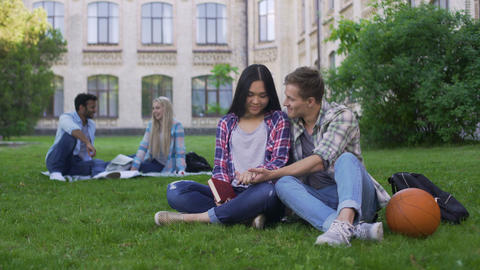 Romantic multiracial couple sitting on lawn near academy and enjoying each other Footage