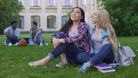 Best friends sitting on lawn near college and talking, support and friendship Footage