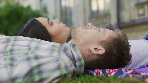 Close-up of mixed race couple lying on grass and enjoying date, tenderness, love Footage