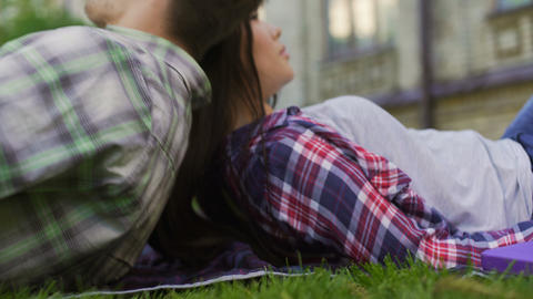 Loving couple of mixed-race teens lying on lawn, enjoying date. First love Footage