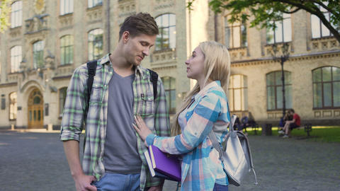 Cheerful couple of students joking and talking near university, relationship Footage
