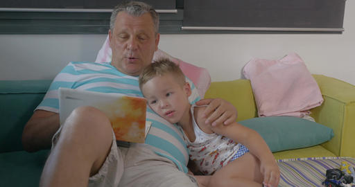 Grandfather and grandchild with laptop at home Footage