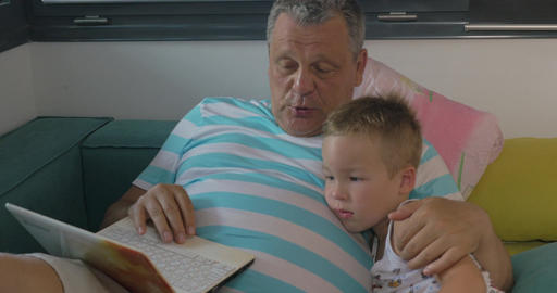 Child and grandfather using laptop at home Footage