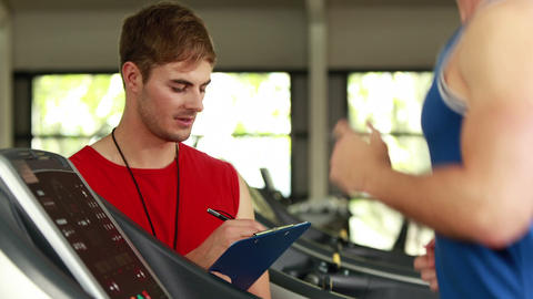 Male trainer writing about treadmill performance Footage