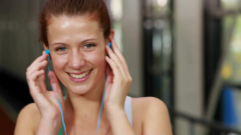 Fit woman putting earphones to listen to music Footage