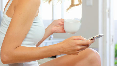 Woman drinking coffee and using smartphone Footage